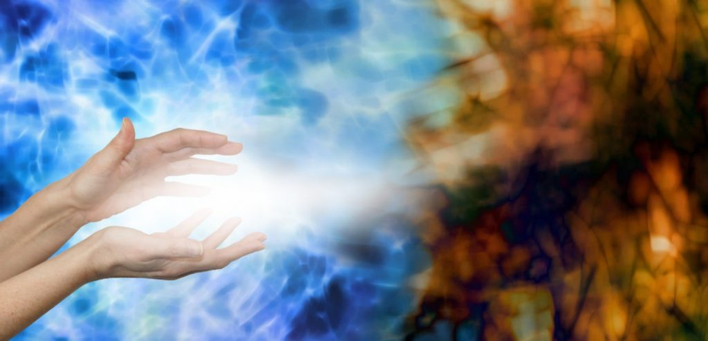 Dispersing Negative Energies -  Female hands on water blue background with stream of white energy between hands appearing to disperse mucky brown energy field on right hand side